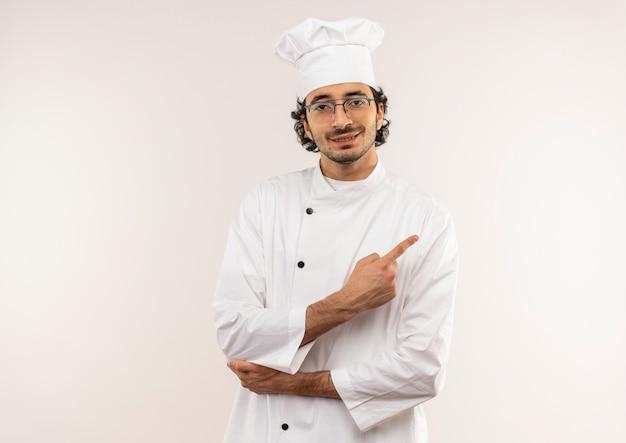 シェフの制服と眼鏡を身に着けている若い男性料理人がコピースペースで白い壁に隔離された側を指していることを喜んで