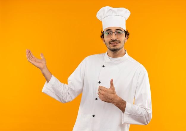 シェフのユニフォームと眼鏡を身に着けている若い男性料理人が親指を上に向けて手でポイントを喜んで