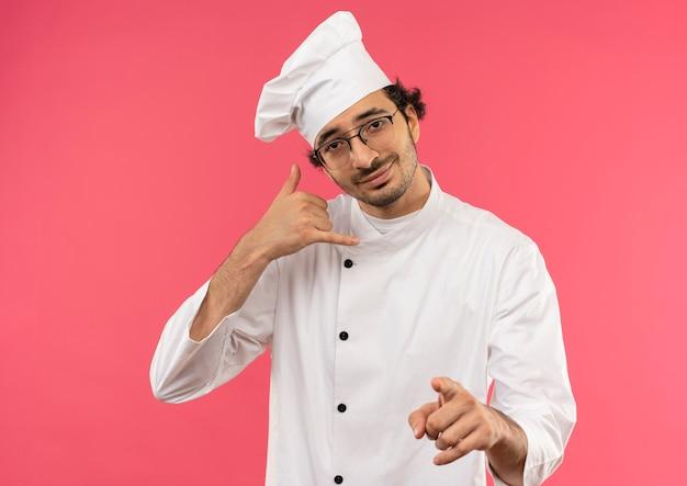 ピンクのジェスチャーで電話のジェスチャーを示すシェフの制服と眼鏡を身に着けている若い男性料理人を喜ばせる