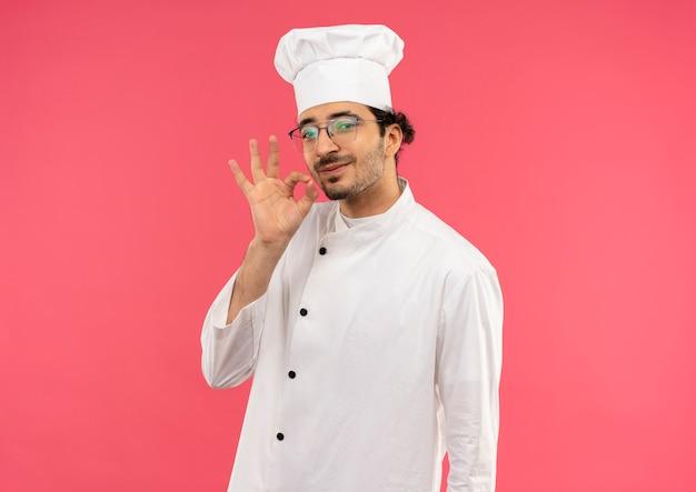 ピンクの壁に隔離されたおいしいジェスチャーを示すシェフの制服と眼鏡を身に着けている若い男性料理人を喜ばせる