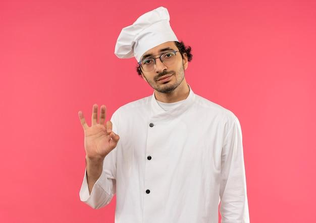 ピンクの壁に隔離されたオーケーのジェスチャーを示すシェフの制服と眼鏡を身に着けている若い男性料理人を喜ばせる