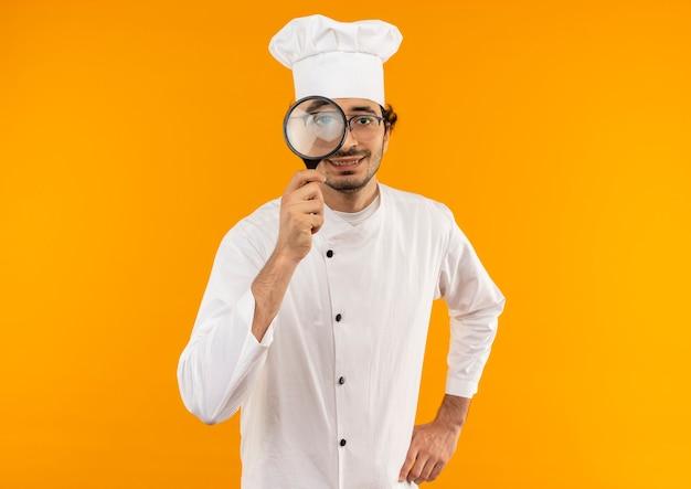 黄色の壁に隔離された拡大鏡とシェフの制服と眼鏡を身に着けている若い男性料理人を喜ばせる