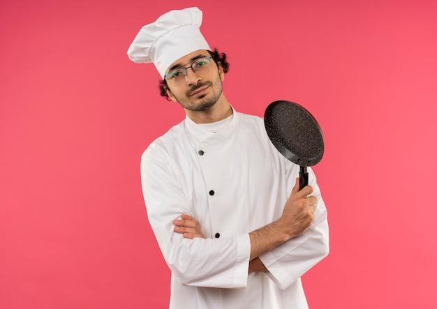 Soddisfatto giovane cuoco maschio che indossa l'uniforme dello chef e occhiali che attraversano le mani e tenendo la padella sul rosa