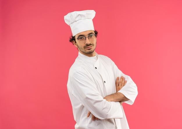 Lieto giovane cuoco maschio che indossa l'uniforme dello chef e bicchieri attraversando le mani