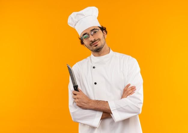 Soddisfatto giovane cuoco maschio che indossa l'uniforme dello chef e bicchieri tenendo il coltello e incrocio le mani isolate sulla parete gialla