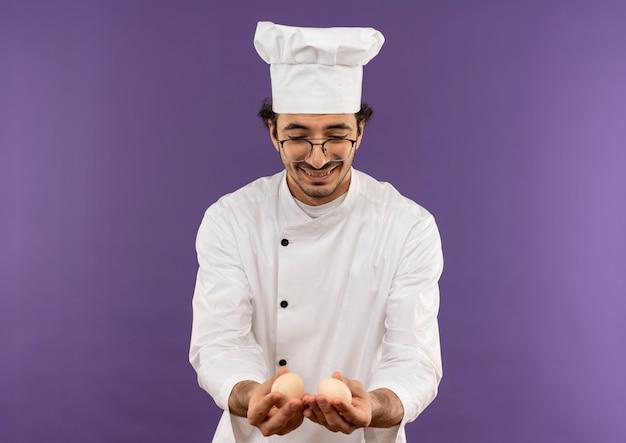 Soddisfatto giovane cuoco maschio che indossa l'uniforme dello chef e bicchieri tenendo e guardando le uova sulla porpora