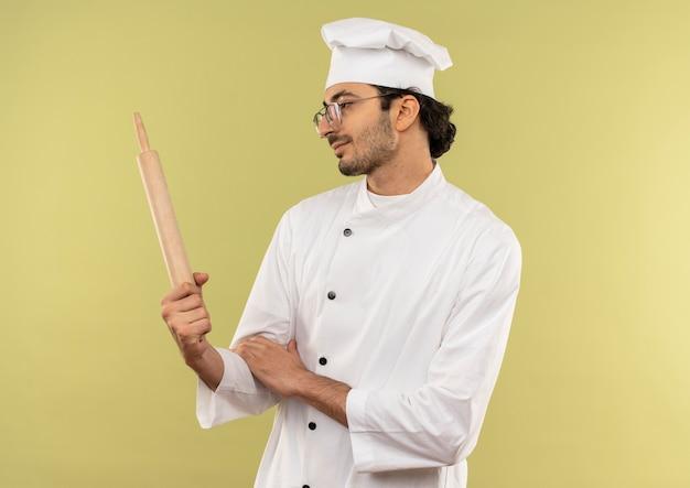 Lieto giovane cuoco maschio che indossa l'uniforme dello chef e bicchieri tenendo e guardando il mattarello isolato sulla parete verde