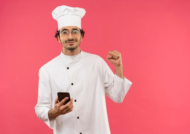 Soddisfatto giovane cuoco maschio che indossa l'uniforme dello chef e bicchieri tenendo il telefono e mostrando il gesto di sì isolato sulla parete rosa