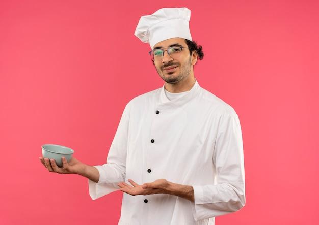 Soddisfatto giovane cuoco maschio che indossa l'uniforme del cuoco unico e occhiali che tengono e punti con la mano alla ciotola isolata sulla parete rosa