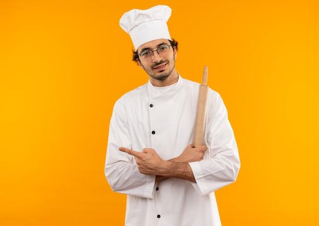 Soddisfatto giovane cuoco maschio che indossa l'uniforme dello chef e bicchieri tenendo il mattarello e incrociando le mani e punti a lato isolato sulla parete gialla con lo spazio della copia