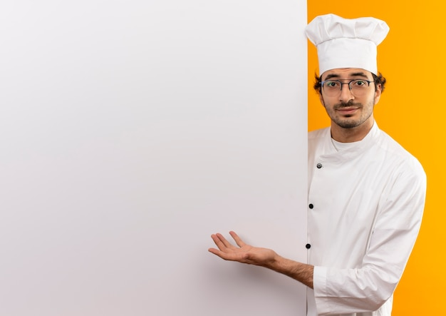 Felice giovane cuoco maschio che indossa l'uniforme del cuoco unico e occhiali che tengono e che mostra con la parete bianca della mano isolata sulla parete gialla con lo spazio della copia