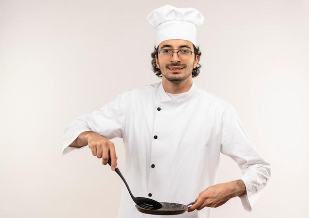 Soddisfatto giovane cuoco maschio che indossa l'uniforme dello chef e bicchieri tenendo la spatola e la padella isolato sul muro bianco