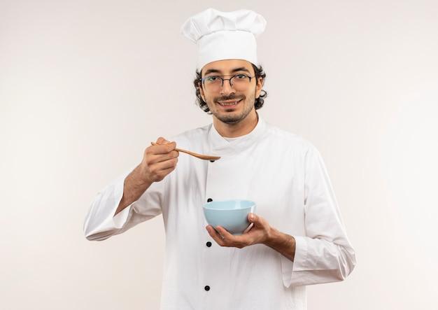 Soddisfatto giovane cuoco maschio che indossa l'uniforme del cuoco unico e bicchieri che tengono cucchiaio con ciotola isolato sul muro bianco