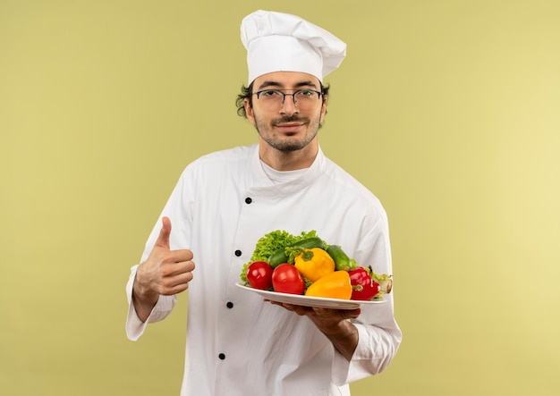 Pleased young male cook wearing chef uniform and glasses holding vegetables on plate his thumb up isolated on green wall