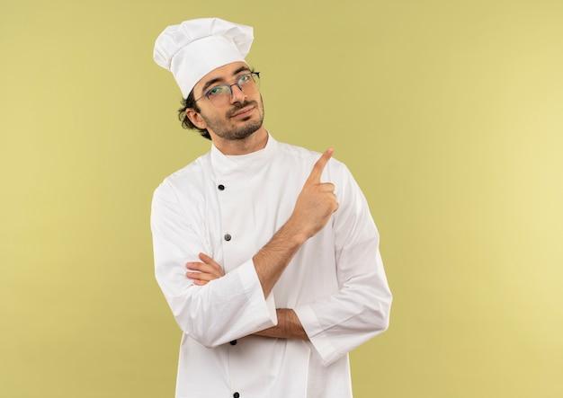 Lieto giovane cuoco maschio che indossa l'uniforme dello chef e gli occhiali indica a lato