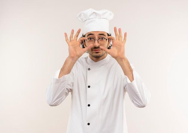 Soddisfatto giovane cuoco maschio che indossa l'uniforme dello chef e bicchieri mettendo la mano sui bicchieri isolati sul muro bianco