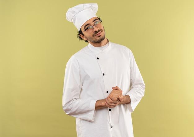 Lieto giovane cuoco maschio che indossa uniforme da chef e bicchieri che mostrano le strette di mano