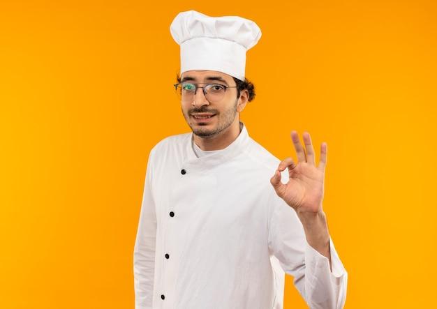 Soddisfatto giovane cuoco maschio che indossa l'uniforme dello chef e occhiali che mostrano il gesto okey isolato sulla parete gialla