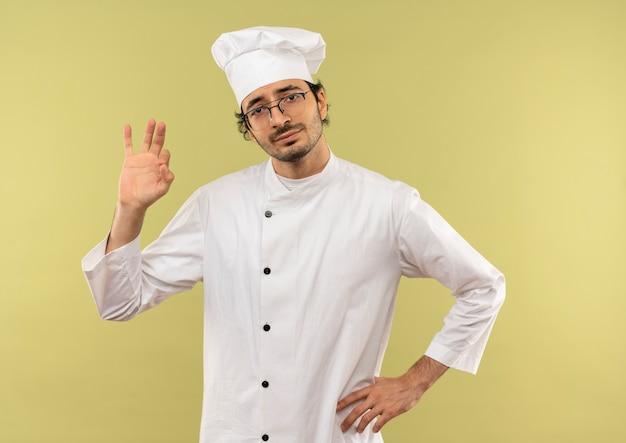 Lieto giovane cuoco maschio che indossa l'uniforme dello chef e bicchieri che mostrano il gesto okey e mettendo la mano sul fianco