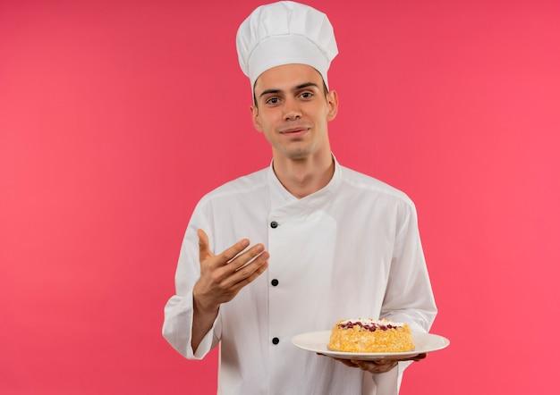Felice giovane cuoco maschio indossando chef uniforme tenendo la torta sul piatto con copia spazio