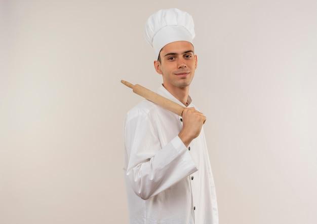 Довольный молодой мужчина-повар в униформе шеф-повара держит скалку на плече с копией пространства
