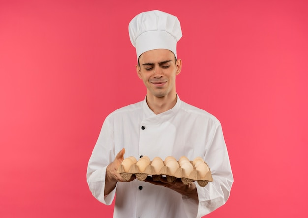 Pleased young male cook wearing chef uniform looking at batch of eggs in his hand