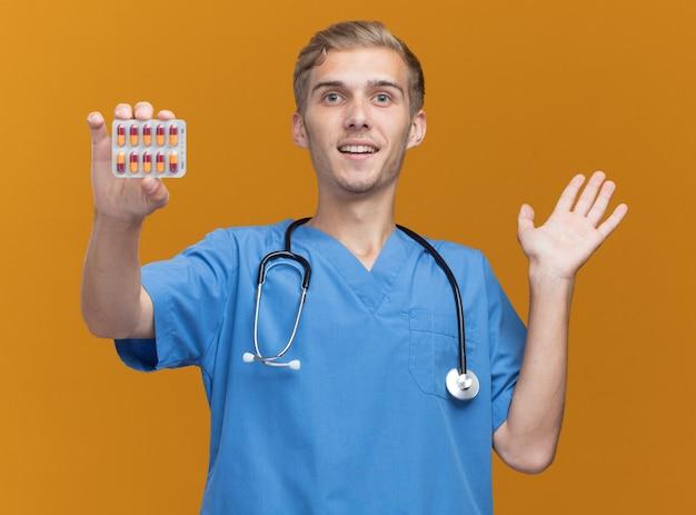 오렌지 벽에 고립 된 손을 확산 약을 들고 청진기로 의사 유니폼을 입고 기쁘게 젊은 남성 의사
