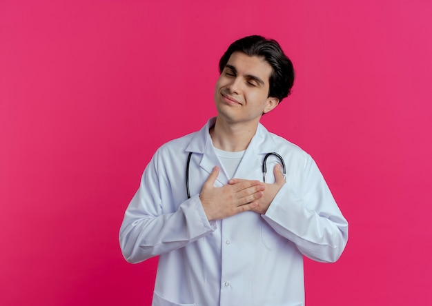 Pleased young male doctor wearing medical robe and stethoscope keeping hands on heart with closed eyes isolated on pink wall with copy space