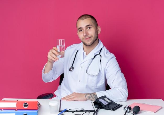 Felice giovane maschio medico indossando abito medico e stetoscopio seduto alla scrivania con strumenti di lavoro tenendo il bicchiere d'acqua mettendo la mano sullo scrittorio isolato sul muro rosa