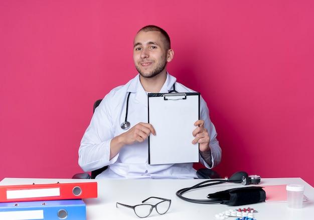 Soddisfatto giovane medico maschio che indossa veste medica e stetoscopio seduto alla scrivania con strumenti di lavoro che mostrano appunti isolato sulla parete rosa