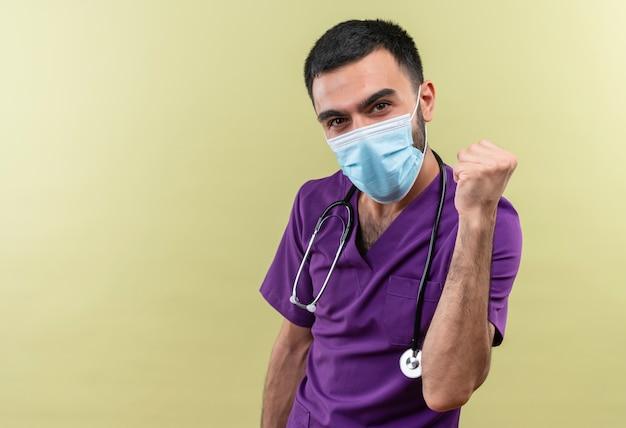 紫色の外科医の服と聴診器の医療マスクを身に着けている若い男性医師は、孤立した緑の背景にイエスのジェスチャーを示して喜んでいます