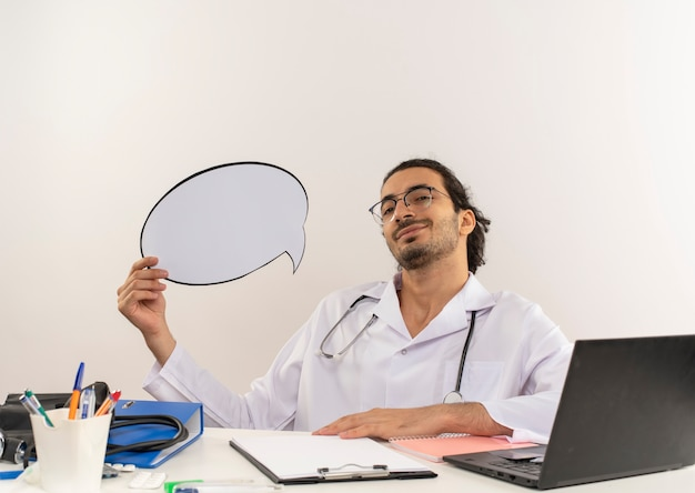 Soddisfatto giovane medico maschio con occhiali medicali che indossa veste medica con stetoscopio