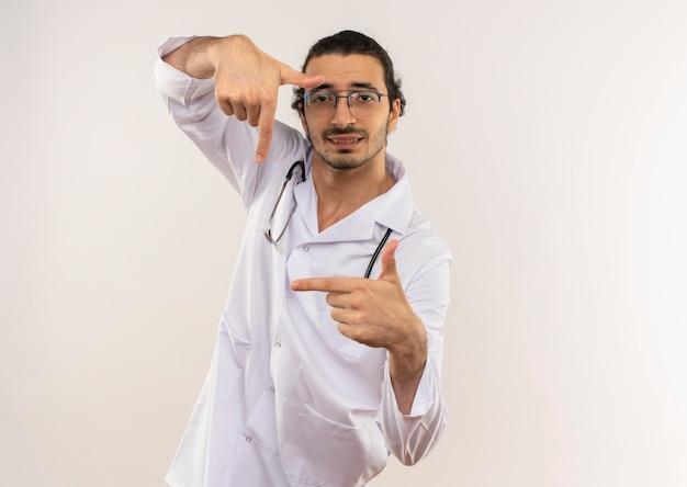 Soddisfatto giovane medico maschio con occhiali ottici che indossa una veste bianca con lo stetoscopio che mostra il gesto della foto sulla parete bianca isolata con lo spazio della copia