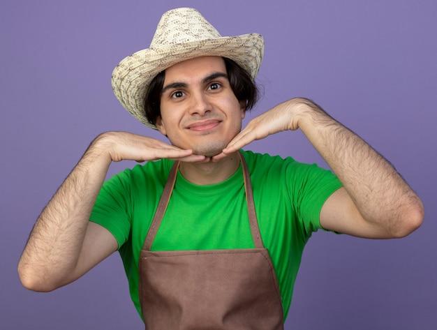 보라색에 고립 된 턱 아래 손을 잡고 원예 모자를 쓰고 제복을 입은 기쁘게 젊은 남성 정원사