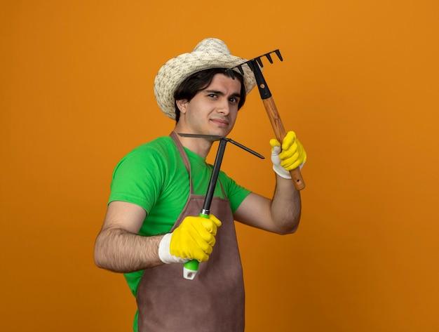 괭이 갈퀴와 갈퀴를 들고 포즈 싸움에 서 장갑과 원예 모자를 쓰고 제복을 입은 기쁘게 젊은 남성 정원사