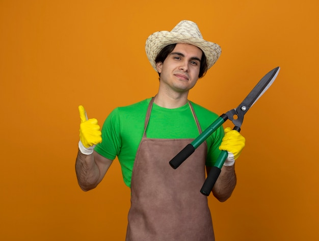 Pleased young male gardener in uniform wearing gardening hat with gloves holding clippers showing thumb up isolated on orange