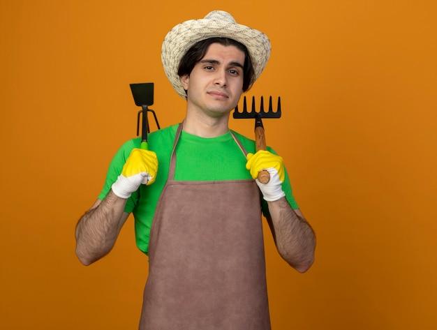 Lieta giovane giardiniere maschio in uniforme che indossa cappello da giardinaggio con guanti tenendo il rastrello con la zappa rastrello sulla spalla isolato su arancione