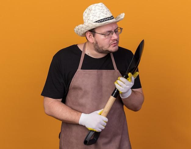 オレンジ色の壁に隔離されたスペードを保持し、見てガーデニングの帽子と手袋を身に着けている若い男性の庭師を喜ばせる