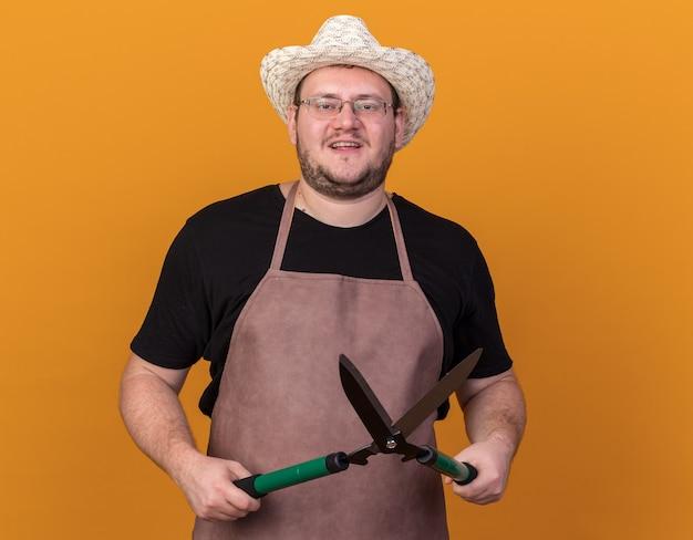 Felice giovane giardiniere maschio che indossa guanti e cappello da giardinaggio tenendo clippers isolato sulla parete arancione