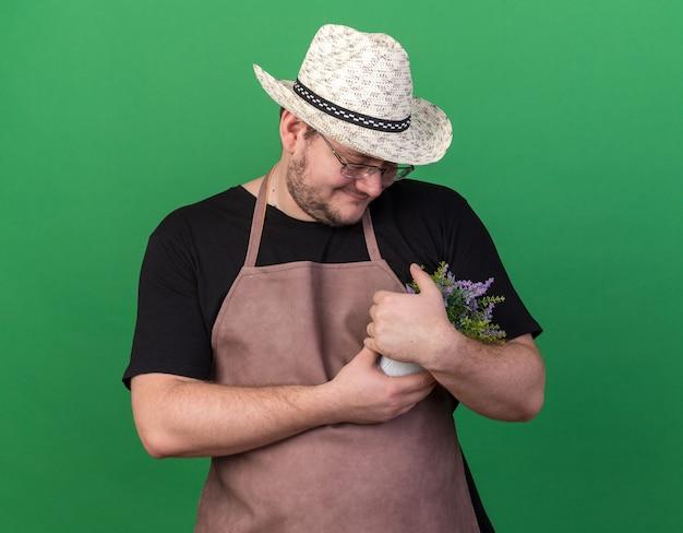 Felice giovane giardiniere maschio che indossa il cappello da giardinaggio afferrato e guardando il fiore in vaso di fiori isolato sulla parete verde