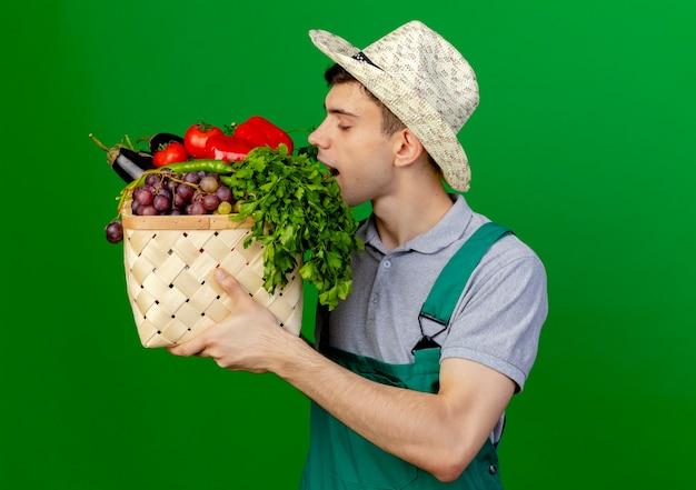 コピースペースで緑の背景に分離された野菜のバスケットを保持し、嗅ぐガーデニング帽子を身に着けている若い男性の庭師を喜ばせる