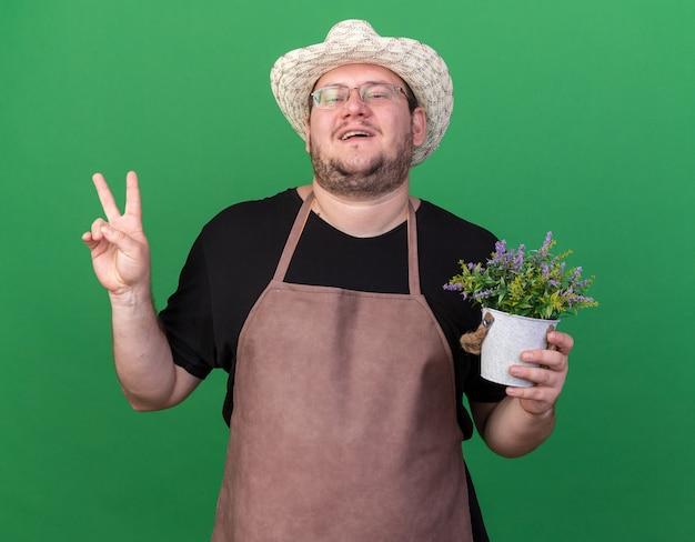 緑の壁に分離された平和のジェスチャーを示す植木鉢に花を保持しているガーデニング帽子を身に着けている若い男性の庭師を喜ばせる