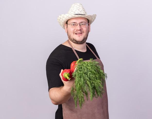 Felice giovane giardiniere maschio che indossa il cappello da giardinaggio tenendo fuori i peperoni con aneto nella parte anteriore isolata sul muro bianco