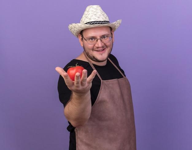 Felice giovane giardiniere maschio che indossa cappello da giardinaggio tenendo fuori il pomodoro isolato sulla parete blu