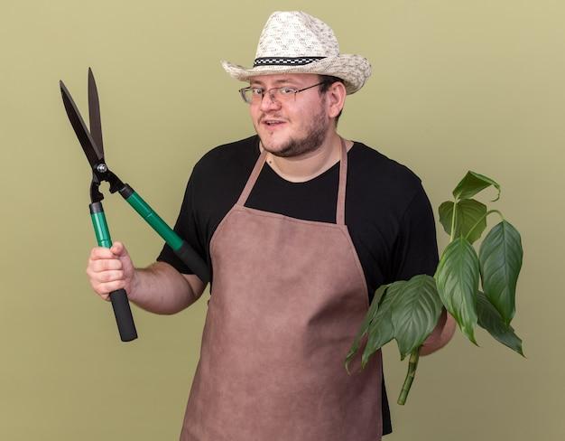 Felice giovane giardiniere maschio che indossa cappello da giardinaggio che tiene pianta con forbici isolate su parete verde oliva