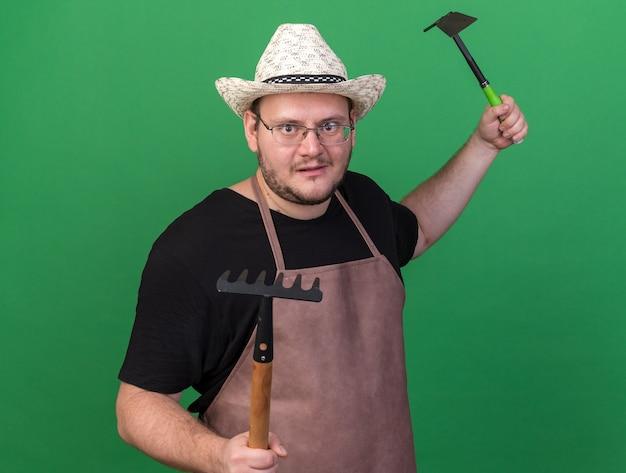 녹색 벽에 고립 된 포즈 싸움에 서 괭이 레이크와 갈퀴를 들고 원예 모자를 쓰고 기쁘게 젊은 남성 정원사