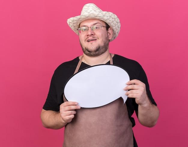 Felice giovane giardiniere maschio che indossa cappello da giardinaggio tenendo il fumetto isolato su parete rosa