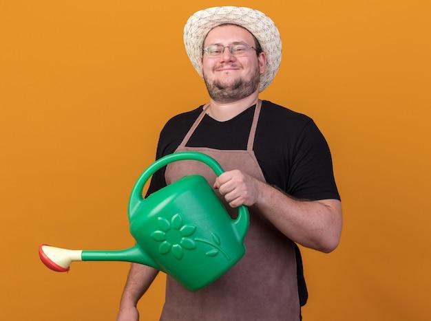 オレンジ色の壁にじょうろを保持しているガーデニング帽子をかぶって喜んで若い男性の庭師