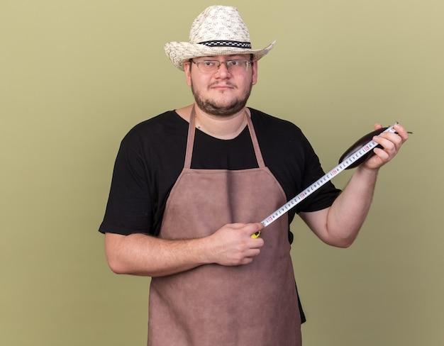 オリーブ グリーンの壁に巻尺でナスを測る園芸帽子をかぶった若い男性庭師が喜んで