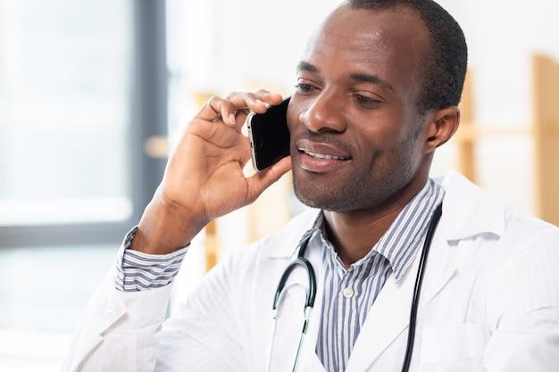 電話で話している間彼の顔に笑みを浮かべて喜んでいる若い男性